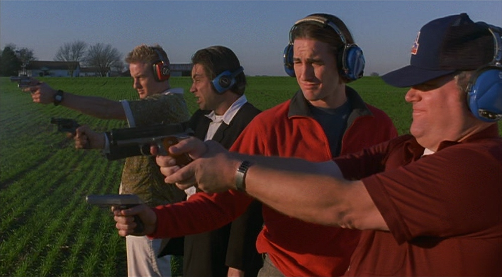 Four men practice shooting a gun