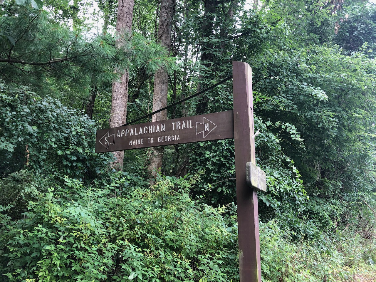 "Photo of the Appalachian Trail sign post, reads ""Maine to Georgia"" with South and North directional arrows"