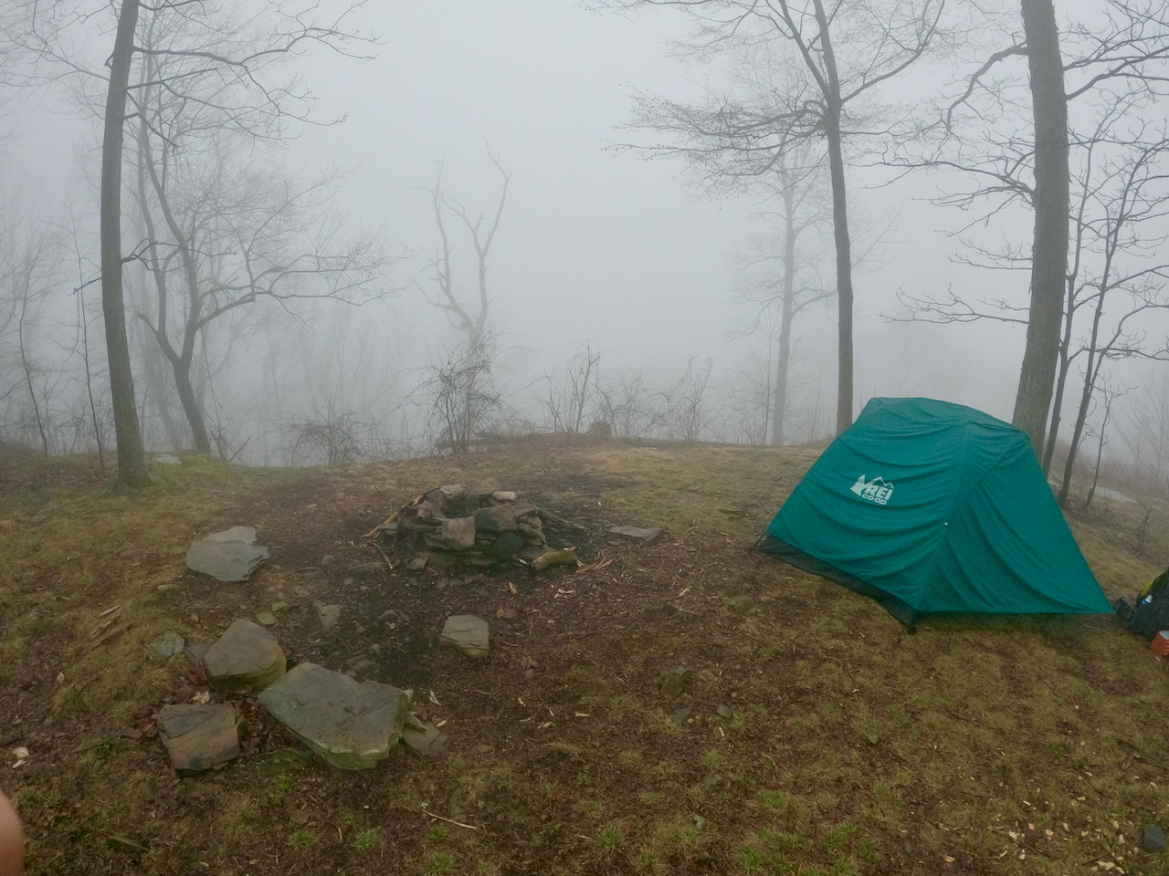 Photo of a primitive fire ring and tent surrounded by fog