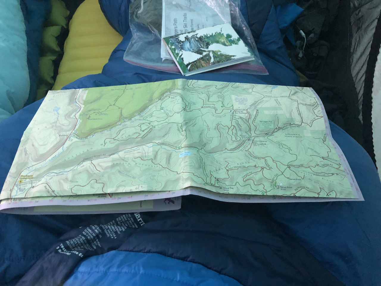 Photo of map and guide book on a sleeping bag