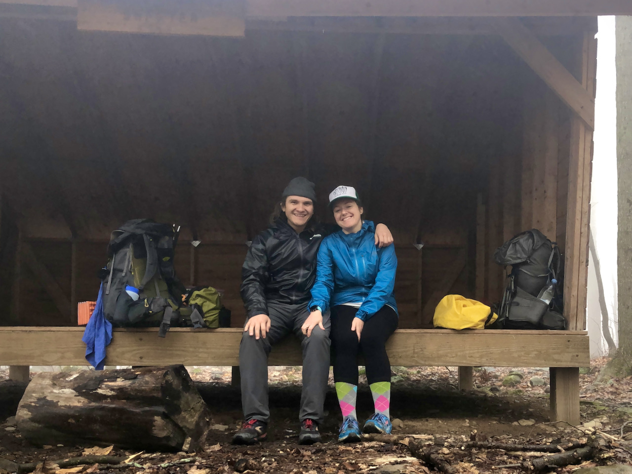 Photo of Brett and Becky at the Sprout Point Shelter surrounded by backpacks