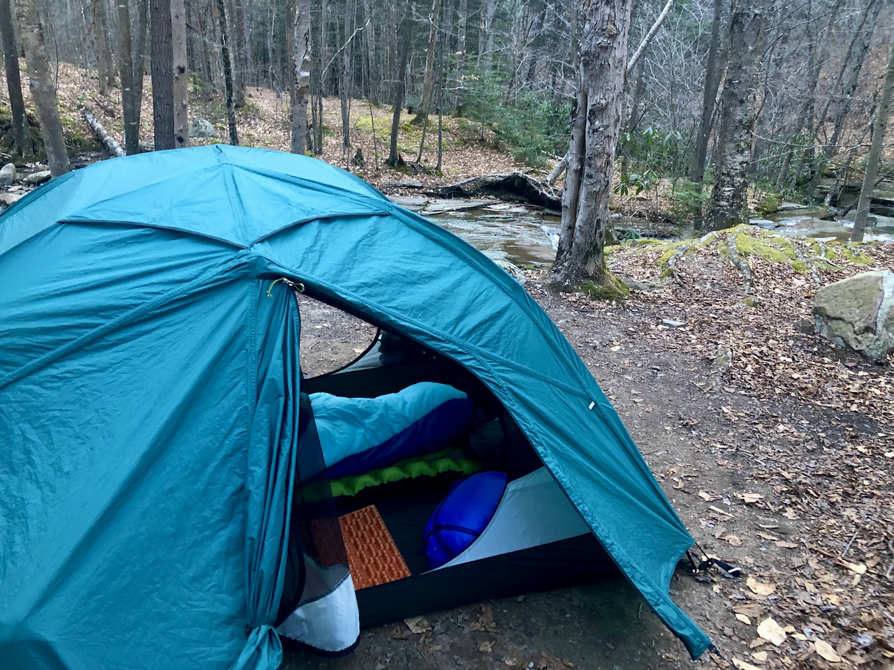 Photo of a setup tent with the door open placed in front of running water