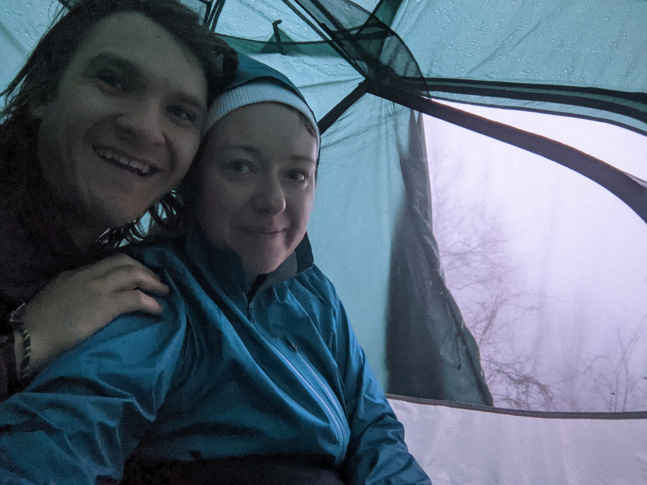 Selfie photo of Brett and Becky in the tent with the door open showing the fog
