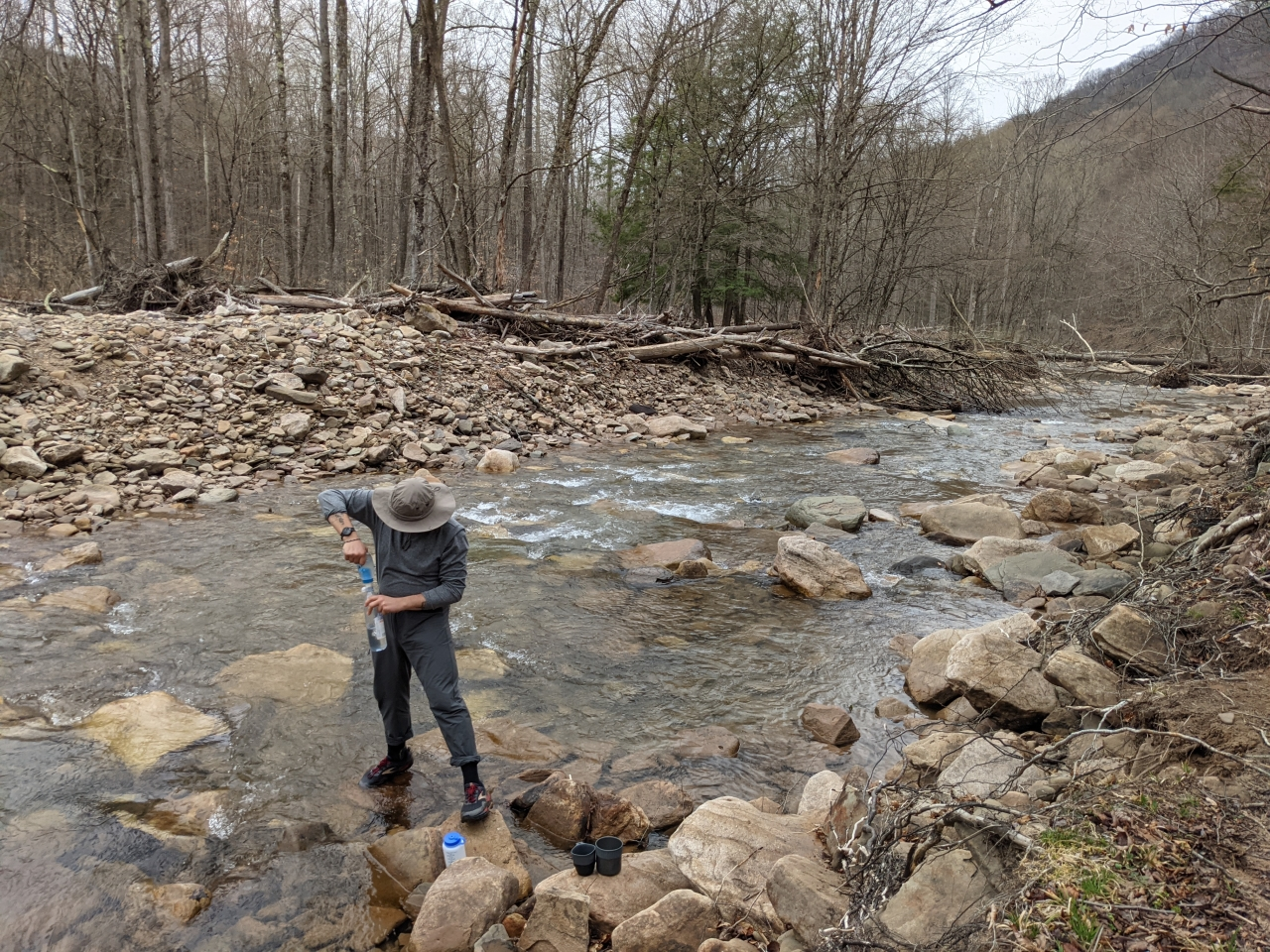Photo of Brett standing in the stream filtering water into a bottle